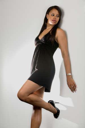 mini jupe: Plein corps de la femme am�ricaine africaine de jeune beau brunette portant la robe noire posant contre un mur