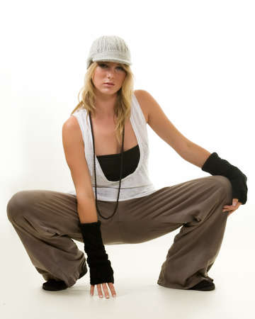 squatting down: Full body of a beautiful blond hair young woman wearing funky hat and arm covering for a funky style squatting down touching the floor on white