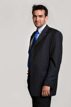 잘 생긴 갈색 머리 젊은 웃는 비즈니스 남자 비즈니스 정장 파란색 넥타이 서있는 입고