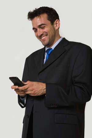 pager: Handsome brunette young laughing business man wearing business suit with blue tie holding and looking at a pager Stock Photo
