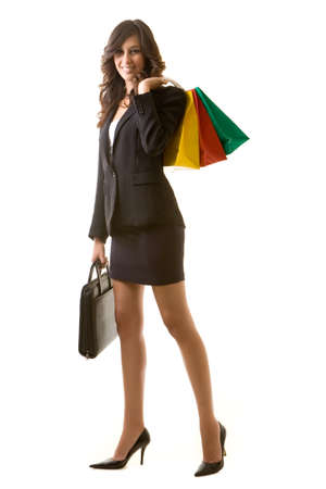 Full body of tall young brunette woman in professional business suit standing on white holding a briefcase and a bunch of colorful shopping bags photo