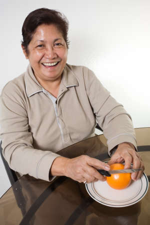 Portrait of a senior asian woman smiling sitting at the kitchen table about to peel and orange Stock Photo - 1535618