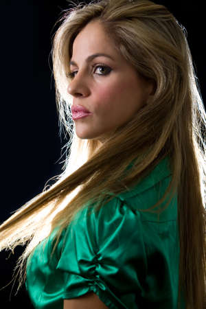 beautiful profile of blond woman face wearing green satin blouse with a serious expression