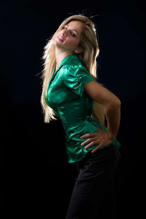 blouse sexy: beautiful young woman with blond hair wearing shiny green satin blouse posing on black background Stock Photo