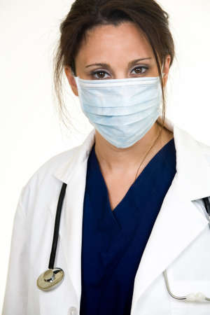 Brunette lady doctor wearing white lab coat with a stethoscope around shoulders and a blue mask over face photo