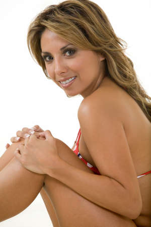 knees up: Pretty Hispanic woman sitting sideways with knees up wearing a swimsuit on white Stock Photo