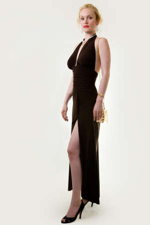 Full body of an attractive woman with hair in bun wearing a long formal black gown with slit showing leg Stock Photo