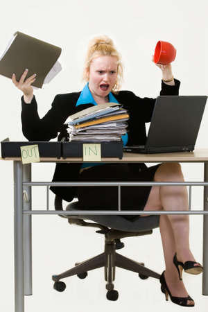 Blond business woman sitting at desk in the office with an overflowing in box holding up a file in one hand and an empty coffee cup in the other with an irritated expression