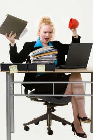 comunicacion no verbal: Rubio negocio mujer sentada en el escritorio en la oficina con una desbordante en la casilla hasta la celebraci�n de un archivo en una mano y una taza de caf� vac�a en el otro con una expresi�n irritada
