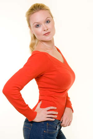 Beautiful blond hair blue eyes woman wearing red sweater and jeans with standing sideways with hand on hip over light colored background Stock Photo - 1612598