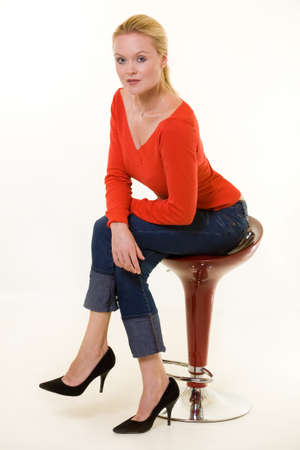 Full body of a blond woman wearing a red sweater and short jeans sitting on a stool with legs crossed photo