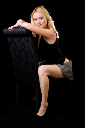 beautiful blond hair woman with sexy legs wearing short mini skirt sitting on black chair over black background 写真素材