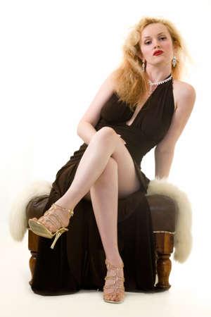 stool: Full body of an attractive blond woman wearing a black formal dress sitting on foot stool with legs crossed looking bored Stock Photo