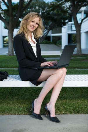 executive assistants: Whole body of an attractive blond business woman wearing a business jacket and a skirt showing sexy legs sitting on a bench outside of an office building typing on a laptop smiling
