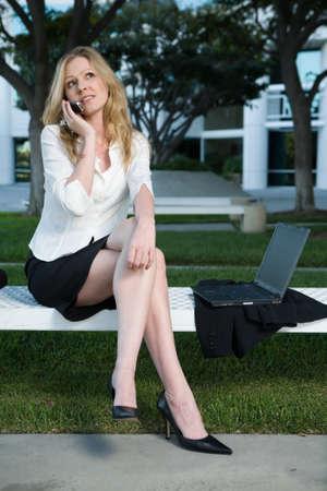 近くのラップトップのオフィスビルの外のベンチに坐っている間携帯電話で話しているセクシーな美脚を示すスカートを着て、ブロンドの魅力的な