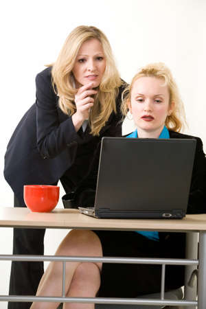 delegar: Dos trabajadores de una oficina de la mujer sentada en un escritorio de pie detr�s de ella tanto busca en la pantalla de un ordenador con graves expresiones