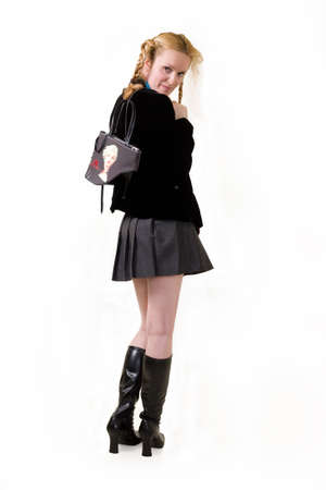 Full body of an attractive woman with hair in braids wearing school girl outfit and long black boots standing  写真素材