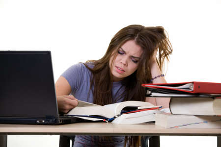 final thoughts: Young woman sitting in front of laptop beside a pile of thick textbooks while reading one with a frustrated stressed expression