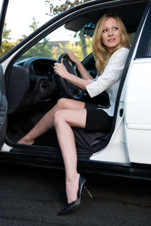 Pretty blond woman in white blouse and black skirt sitting in a white car with one leg out about to get out Stock Photo