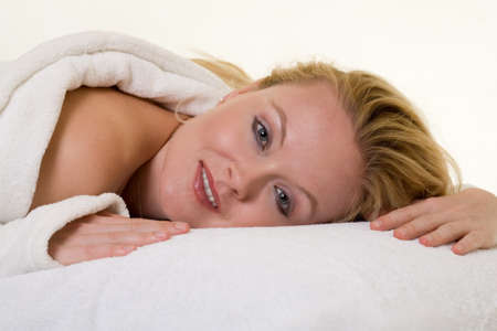 Attractive blond woman laying on stomach on a white pillow wearing white robe