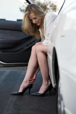 legs open: Pretty blond woman in white blouse and black skirt sitting in a white car with legs out putting on sexy black high heel shoes rubbing sore ankle