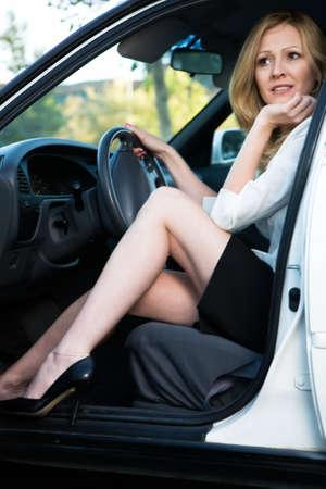 gambe aperte: Donna bionda graziosa in camicetta bianca e pannello esterno nero che si siedono in un automobile bianco con il portello aperto Archivio Fotografico