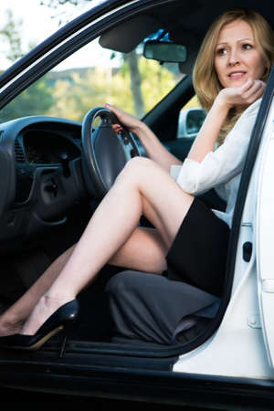 legs open: Pretty blond woman in white blouse and black skirt sitting in a white car with door open