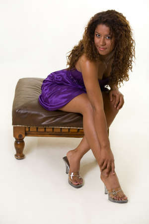 footstool: Whole body of a beautiful brunette Hispanic American young woman with long curly hair wearing purple satin dress sitting on a footstool over white