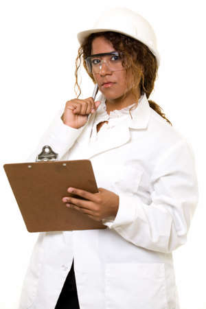 uniform curls: Attractive Hispanic woman in white lab coat and white safety hard hat and safety goggles holding a chart or clipboard on white