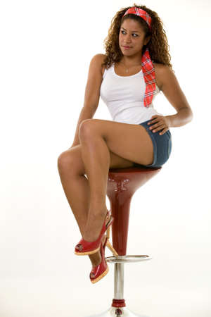 Full body of a young Hispanic woman wearing a jean shorts white tank and red head band sitting on a red bar stool Stock Photo