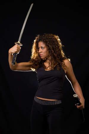 Attractive Hispanic woman wearing all black holding a samurai sword standing on black photo