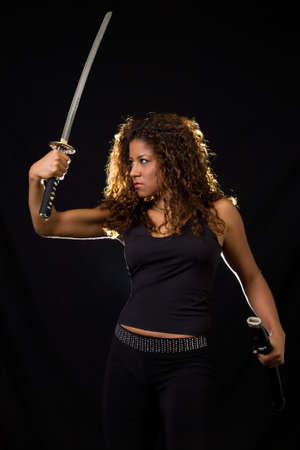 tough: Attractive Hispanic woman wearing all black holding a samurai sword standing on black