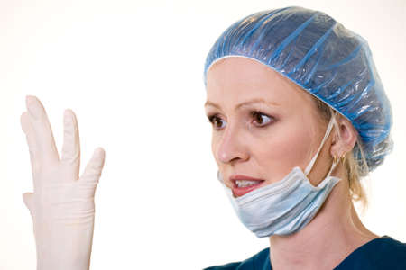 Face of a woman doctor wearing protective hair net and face mask holding up and looking at one hand with a latex glove