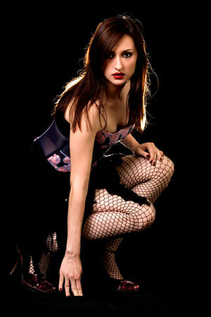 Full body of an attractive long haired brunette woman in black dress kneeling down on black background Stock Photo