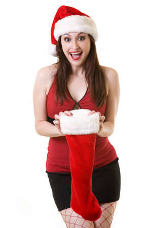 Attractive long haired brunette woman wearing sexy red and black top and short black skirt and santa hat and red fishnet stocking holding on to a Christmas stocking with a happy surprised expression