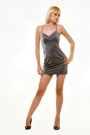 Hele lichaam van een mooie jonge vrouw met blond haar in een sexy korte zilveren jurk die op wit
