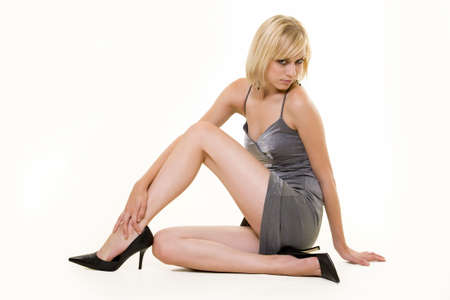 Full body of an attractive young woman with blond hair in a sexy short silver dress sitting on the floor on white