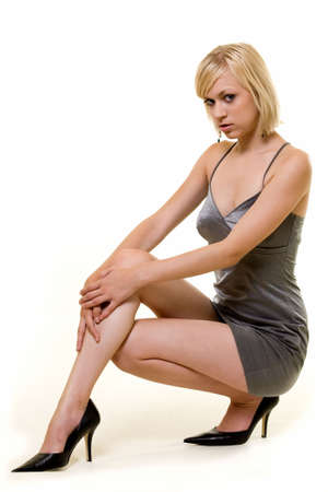 bending down: Full body of an attractive young woman with short blond hair in a sexy short silver dress bending down on white Stock Photo
