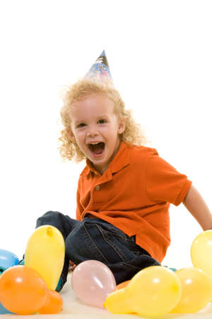 Adorable little three year old boy wearing party hat sitting with balloons with open mouth happy expression photo