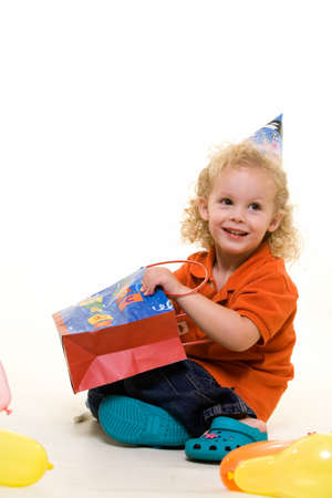 Adorable little three year old boy wearing party hat sitting with balloons with hand in a gift bag Stock Photo - 1806615