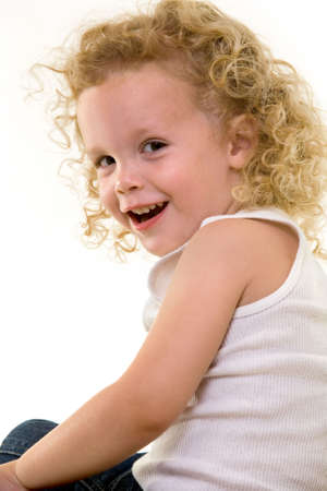 Portrait of an adorable little three year old boy wearing white top sitting on a chair with a curly long blond hair with a cute smile Stock Photo - 1806607