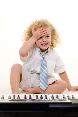 Adorable little three year old boy with long curly blond hair wearing white shirt and tie sitting in front of a piano keyboard with hand on forhead Stock Photo - 1806614