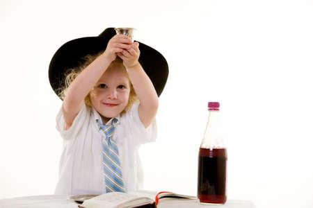 shabat: Retrato de un adorable peque�o ni�o de tres a�os de edad, vestido de blanco sentado en un principio rojo silla con un largo cabello rubio rizado