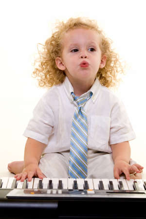 Adorable little three year old boy with long curly blond hair wearing white shirt and tie sitting in front of a piano keyboard on white Stock Photo