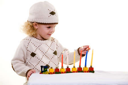 Young blond hair three year old boy lighting the candles in the Jewish tradition to celebrate Hanukkah Stock Photo - 1831383