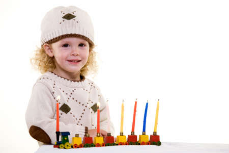 Young blond hair three year old boy lighting the candles in the Jewish tradition to celebrate Hanukkah photo