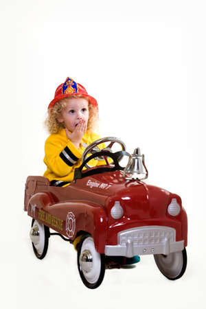 Portrait of an adorable little three year old boy wearing fireman costume sitting in a toy firetruck over white photo