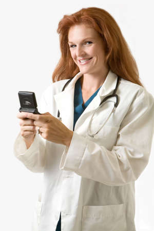 pager: Female attractive red hair doctor wearing white lab coat holding a pager with a smile on her face