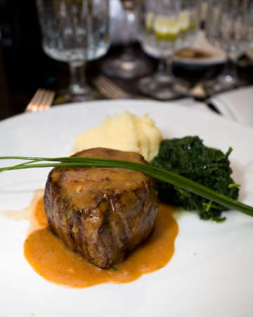 professionally: Macro of a professionally prepared gourmet Filet Mignon served as the main course of a reception