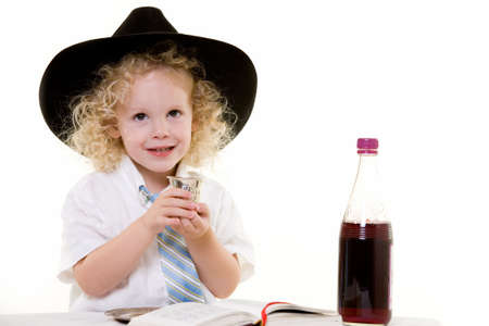 kiddush: Portrait of an adorable curly haired blond little three year old boy wearing white shirt and tie and a black fedora practicing the Jewish Sabbath ritual Stock Photo